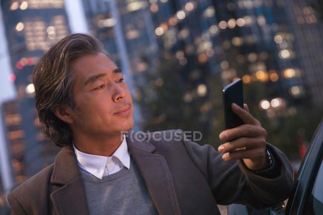 Serio maturo asiatico uomo appoggiato a auto e utilizzando smartphone in notte città — Foto stock