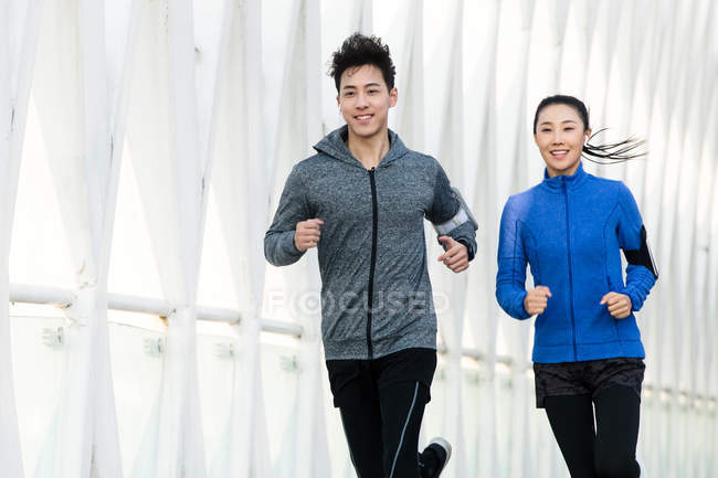 Smiling young asian runners training together outdoor — Stock Photo