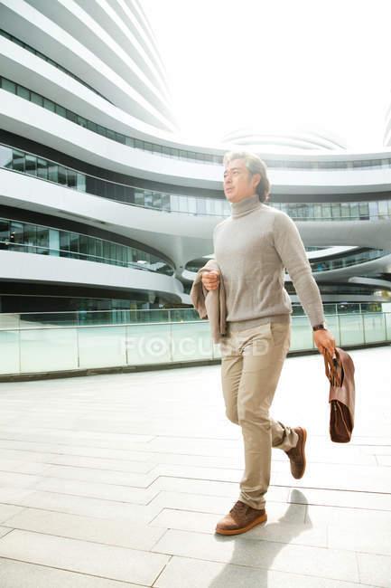 Pleine longueur vue de mature asiatique homme d'affaires tenant mallette et marcher à l'extérieur immeuble de bureaux — Photo de stock