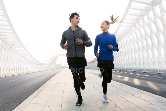 Низкий угол обзора счастливой молодой азиатской пары бегунов, улыбающихся друг другу во время тренировки на мосту — стоковое фото