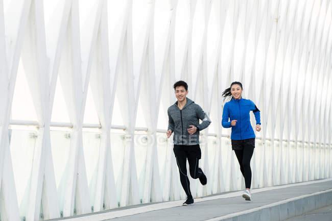 Giovani atleti sorridenti maschi e femmine che fanno jogging insieme sul ponte moderno — Foto stock