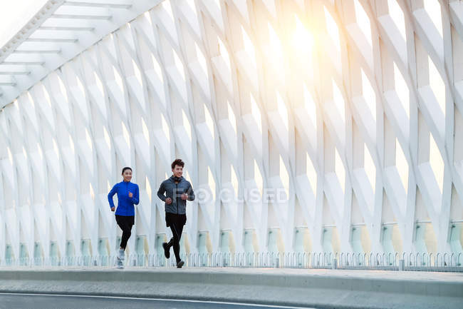 Smiling young asian male and female athletes in sportswear jogging together on modern bridge — Stock Photo