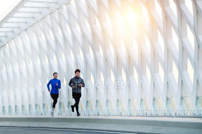 Sonriente joven asiático macho y hembra atletas en sportswear jogging juntos en moderno puente - foto de stock