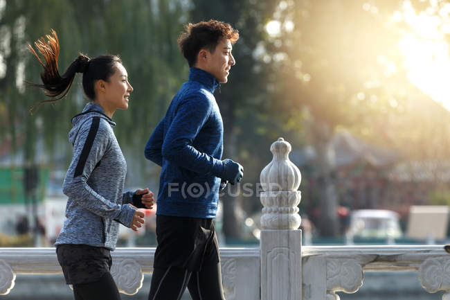 Side view of smiling young asian runners training together outdoor in the morning — Stock Photo