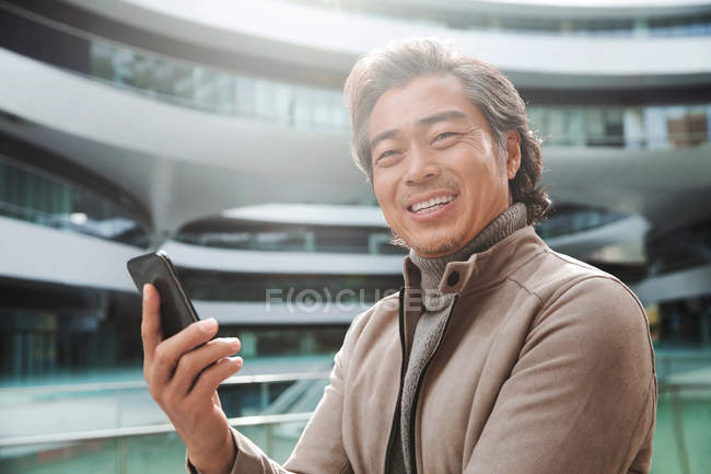 Cheerful mature asian man holding smartphone and smiling at camera — Stock Photo