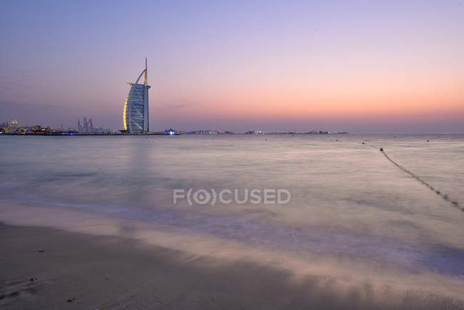 Dubai, United Arab Emirates - Oct 10, 2016: The illuminated Burj Al Arab hotel and marina at dusk, view from Jumeira beach, looking southwest. — Stock Photo