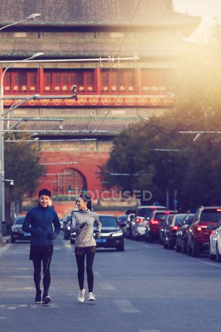 Smiling athletic young couple in sportswear jogging together on street — Stock Photo