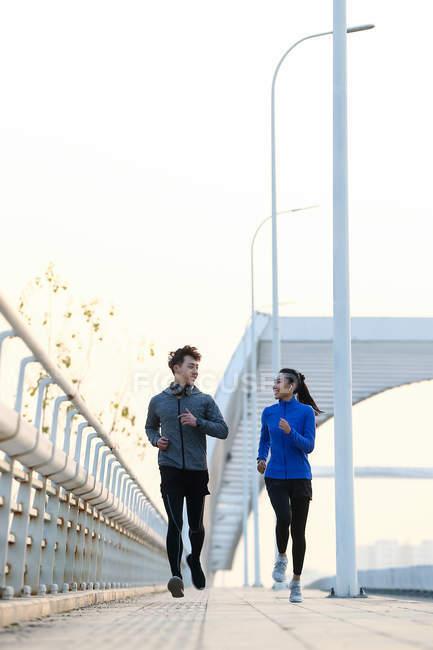 Happy молода азіатська пара усміхнені один одного і пробіжки разом на вулиці — стокове фото