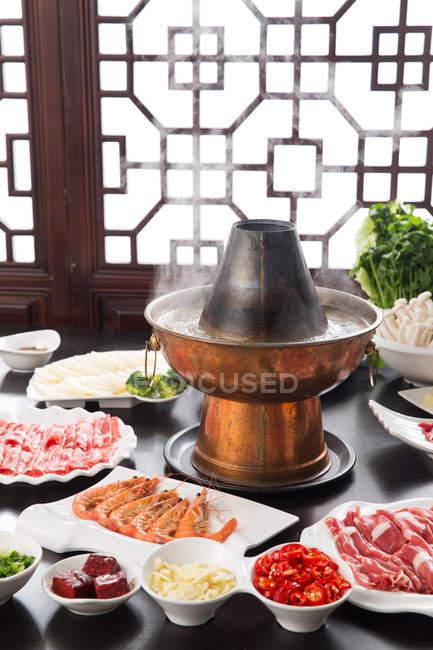 Медь горячий горшок и тарелки с мясом, креветками и овощами на столе, износох блюдо концепции — стоковое фото