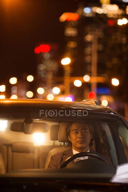 Vista attraverso parabrezza di maturo asiatico uomo guida auto di notte — Foto stock