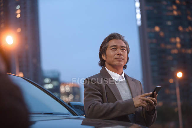 Mature asian man standing beside car and using smartphone at night — Stock Photo