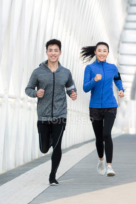 Happy young asian joggers smiling at camera and running together on bridge — Stock Photo