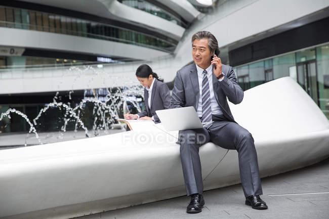 Bello asiatico uomo d'affari utilizzando laptop e parlando da smartphone vicino fontana in moderno business center — Foto stock