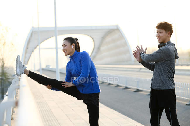 Smiling young male and female athletes stretching during workout on bridge — Stock Photo