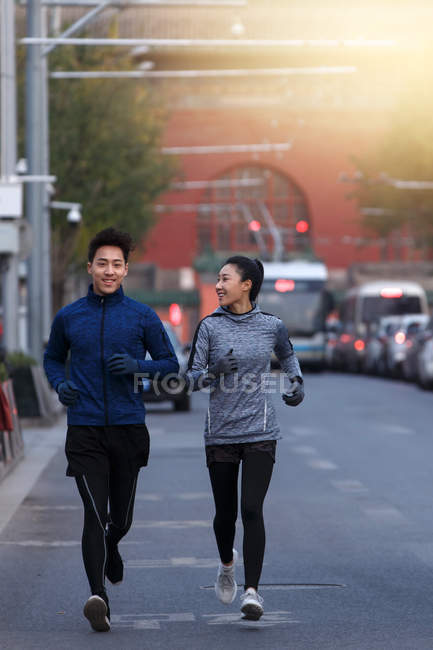 Young male and female athletes in sportswear running together on street — Stock Photo