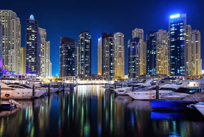 Amazing famous Dubai marina with yachts and skyscrapers reflected in water at night — Stock Photo