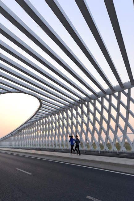 Young male and female athletes running together on modern bridge - foto de stock