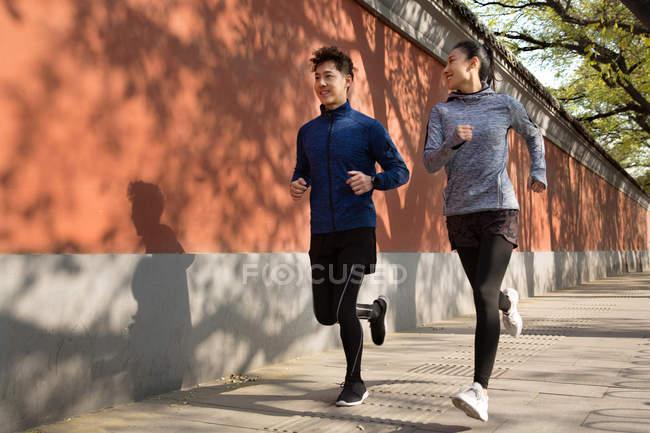 Полный вид молодой азиатской пары в спортивной одежде, улыбающейся и бегающей вместе по улице — стоковое фото