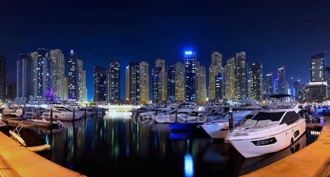 Increíble famoso puerto deportivo de Dubai con yates y rascacielos reflejados en el agua por la noche - foto de stock