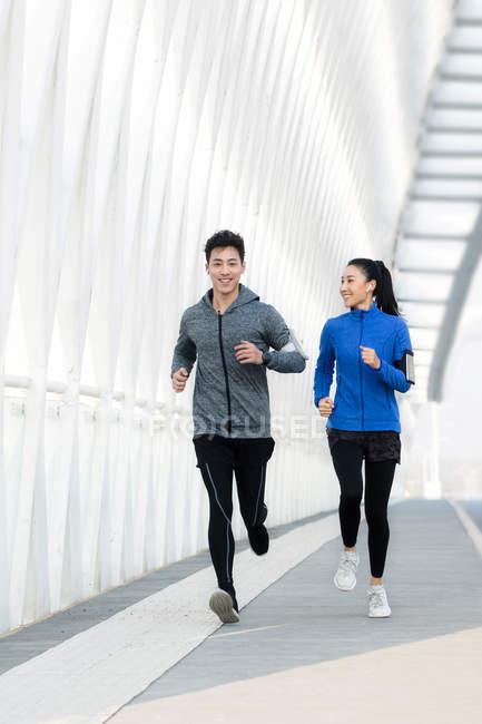 Улыбающаяся юная азиатская спортсменка, смотрящая на своего бойфренда, бегая вместе по мосту — стоковое фото