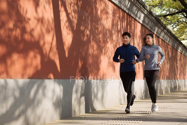 Повна довжина вид посміхаючись молодих азіатських спортсменів і спортсменка працює разом на вулиці — стокове фото