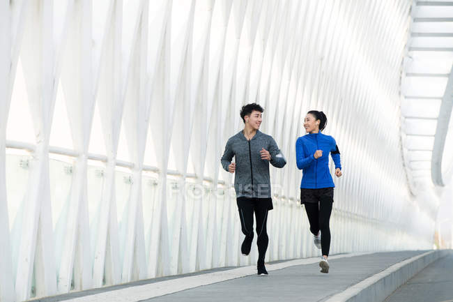 Sporty young asian couple smiling each other and running together on bridge — Stock Photo