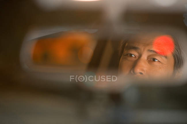 Spiegelung im Spiegel eines reifen asiatischen Autofahrers, Nahaufnahme, selektiver Fokus — Stockfoto