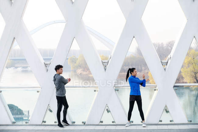 Sporty young asian couple of joggers stretching together during workout on bridge — Stock Photo