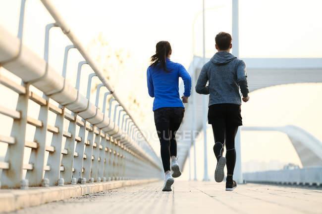 Назад вид пара бігунів працюють разом на мосту — стокове фото