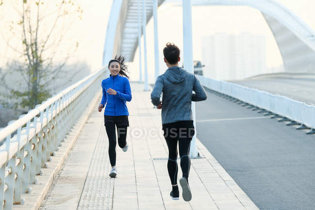 Young sportsman and sportswoman running on bridge — Stock Photo