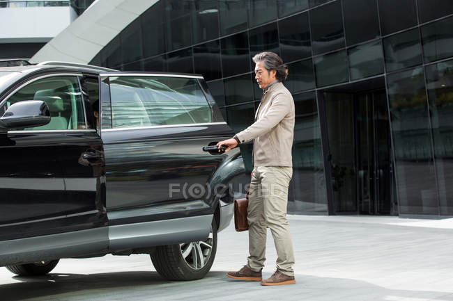 Full length view of mature asian businessman holding briefcase and opening car door — Stock Photo