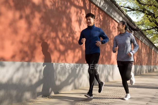 Full length view of sporty young couple running together on street — Stock Photo