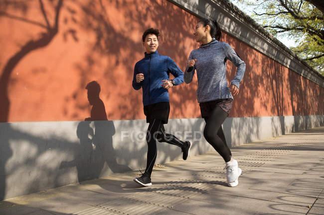 Deportivo joven asiático pareja sonriendo cada otro y jogging juntos en calle - foto de stock