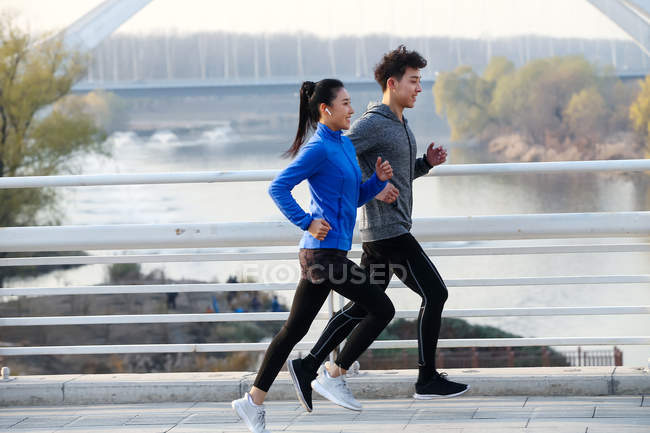 Side view of young asian couple of athletes running together near river — Stock Photo