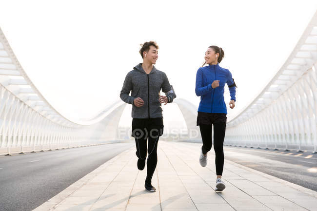Young male and female athletes smiling each other and jogging together — Stock Photo