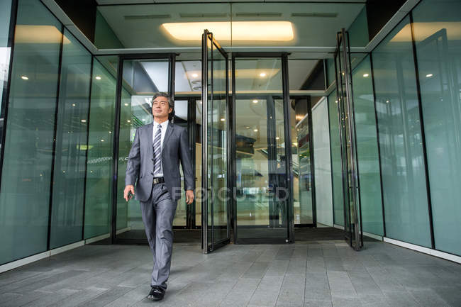 Full length view of mature asian businessman in formal wear near office building — Foto stock
