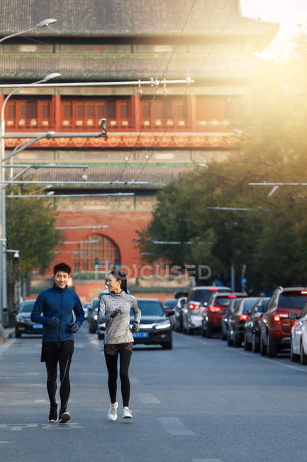 Full length view of smiling young asian joggers training together on street - foto de stock