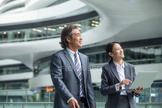 Uomini d'affari asiatici che camminano con il computer portatile nel moderno centro business — Foto stock
