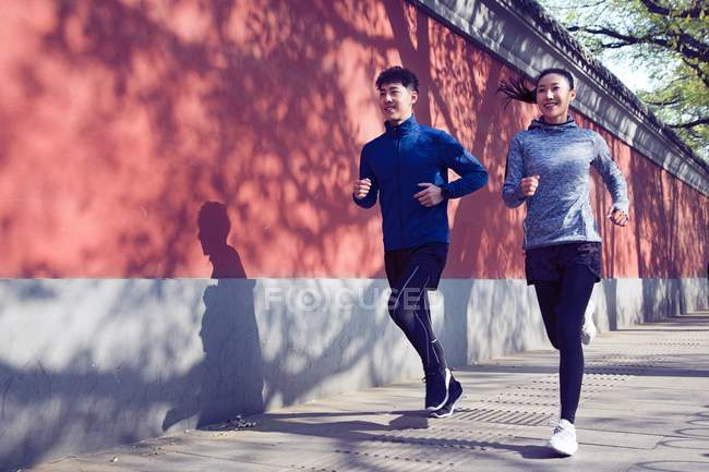 Sporty young couple smiling and running together on street — Stock Photo