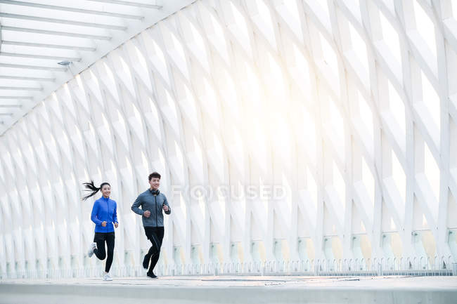 Smiling young asian runners in sportswear training together on bridge — Stock Photo