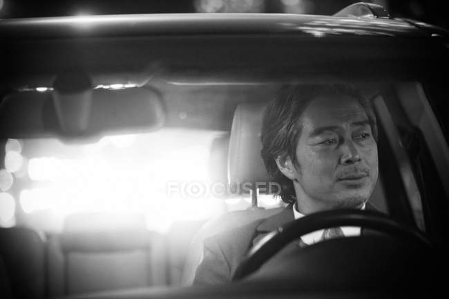 View through windshield of mature asian man driving car, black and white image — Stock Photo