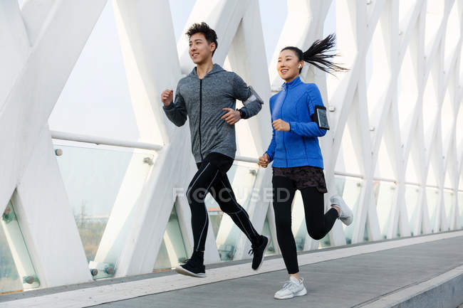 Smiling sporty young asian couple jogging together and looking away outdoor — Stock Photo