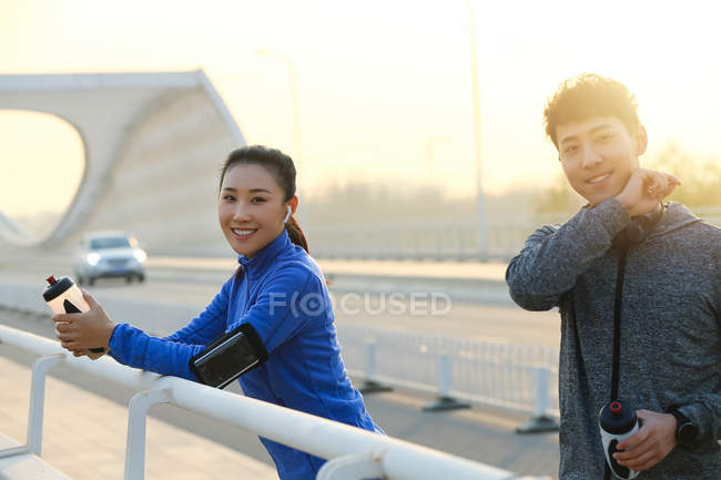 Young asian athletes holding bottles of water and smiling at camera after workout on street — Stock Photo