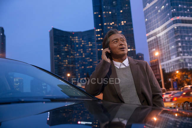 Mature asian man leaning at car and talking by smartphone in night city — Stock Photo