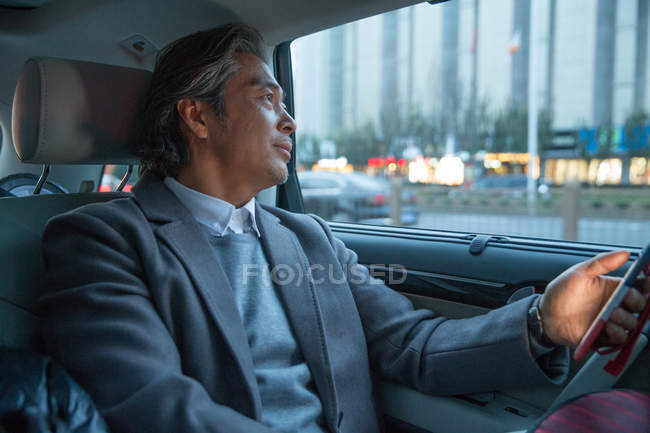 Mature asian businessman using smartphone and looking away in car — Stock Photo