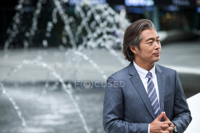 Serious mature asian businessman in formal wear standing near fountains — Stock Photo