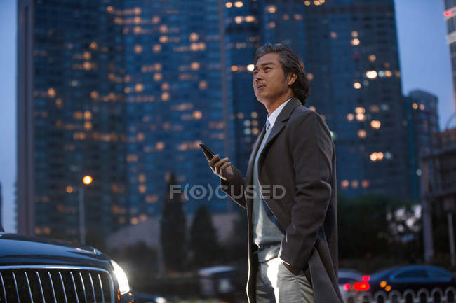Mature asian man standing beside car and holding smartphone in night city — Stock Photo
