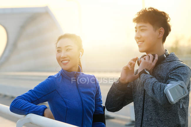 Smiling young asian couple of runners standing on bridge and looking away in the morning — Stock Photo