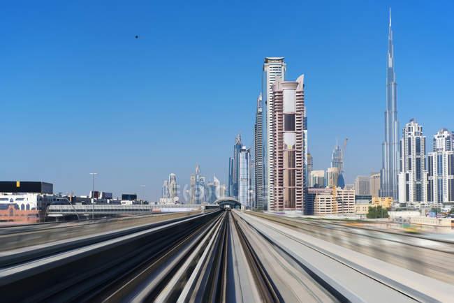 Vista de la línea de metro de Dubai y del moderno paisaje urbano. - foto de stock