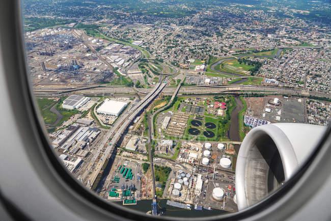 Com vista para a terra e área urbana do avião — Fotografia de Stock